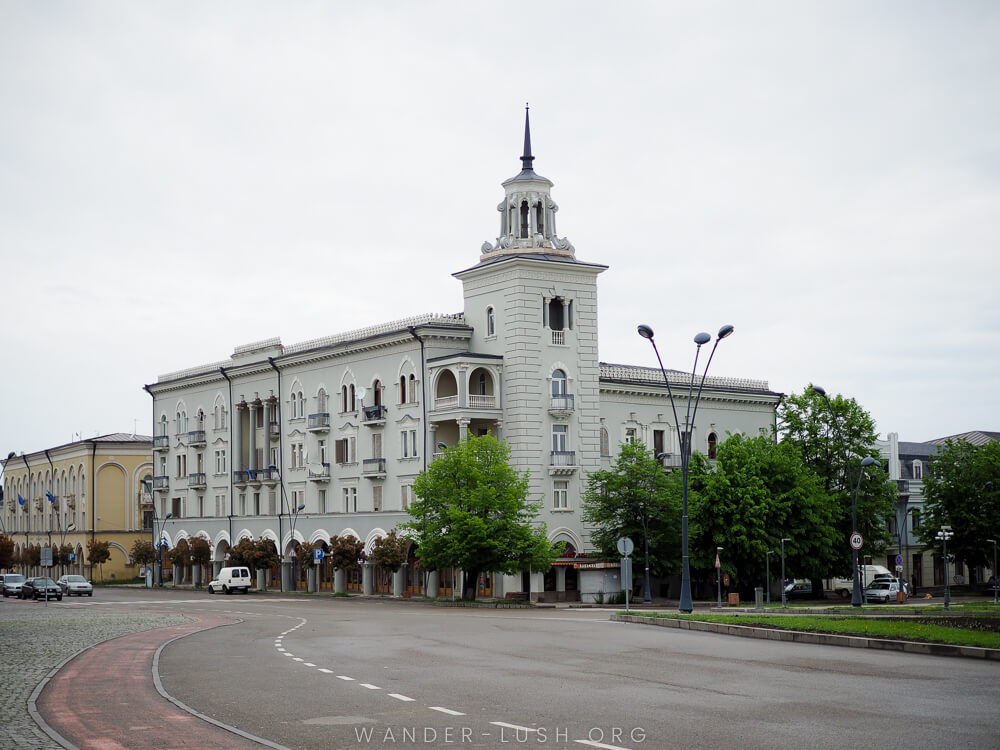 A classical-style grey building at a large road intersection.