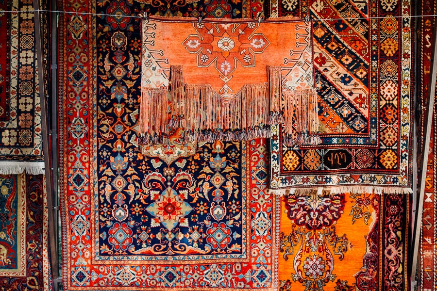 A display of red and pink-tone carpets with Caucasian designs.