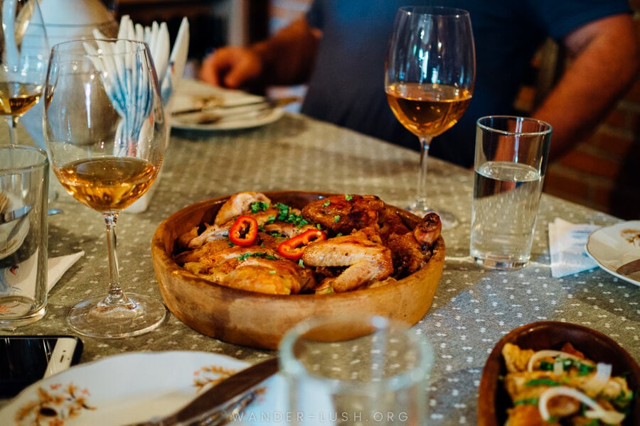 A wooden plate heaped with chicken and surrounded by glasses of amber-coloured wine.