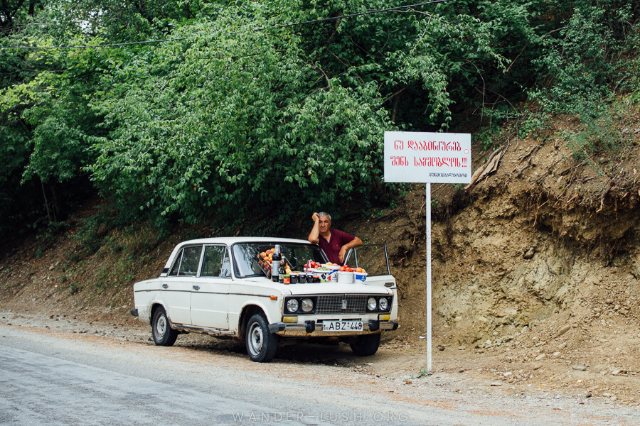 A man on the road from Tbilisi to Sighnaghi, leaning on his car with fresh fruit and jars of jam displayed on the hood.
