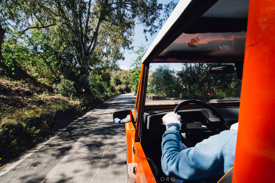 A man in a blue jumper driving a red jeep in the Aeolian Islands.