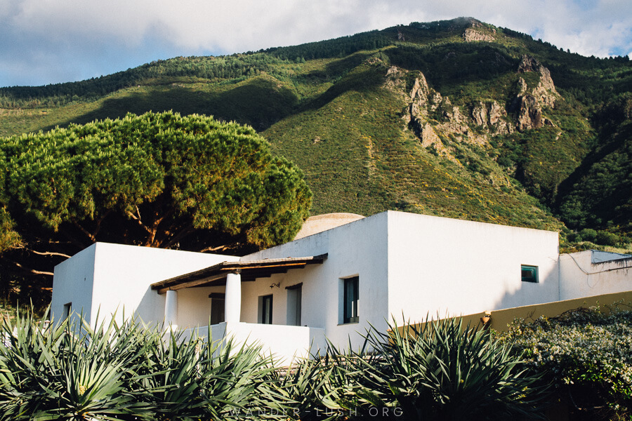 A modern white house nestled beneath a green mountain.