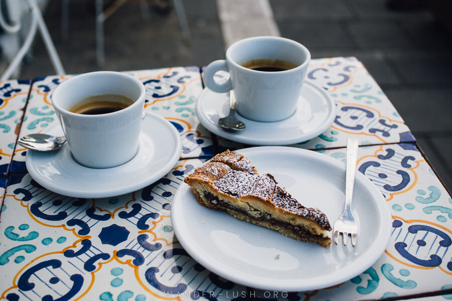 A slice of cake and two cups of coffee sitting on a tiled cafe table.