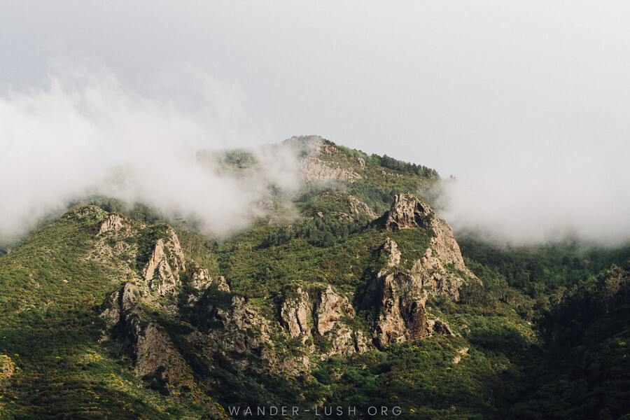 Close up of a rock formation in the Aeolian Islands covered with greenery and wreathed in clouds.