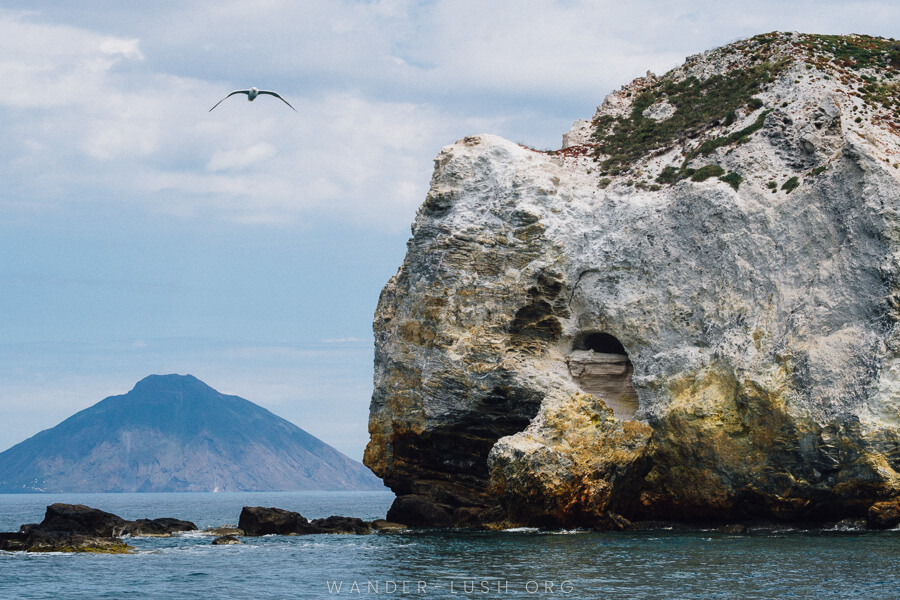 A seagull flies over two rock formations in the ocean.