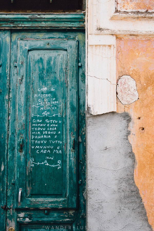 An old green door scribbled with white text in Italian language.