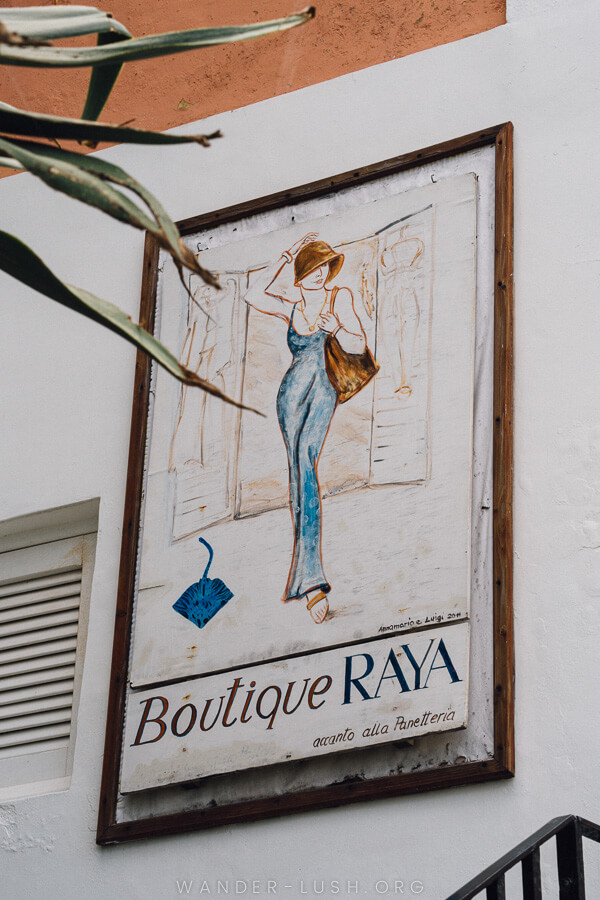A shop sign reading 'Boutique Raya' featuring a woman in a sun hat.