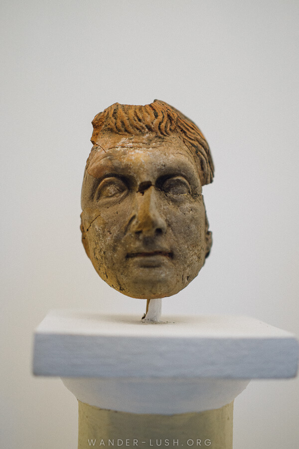 An ancient clay mask depicting a man's face.