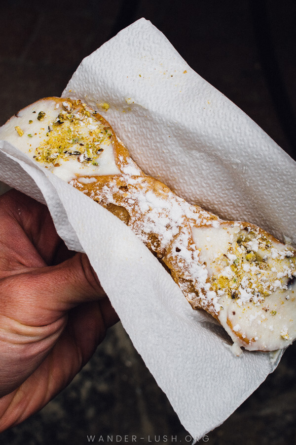 A cannoli topped with ground pistacchio nuts.