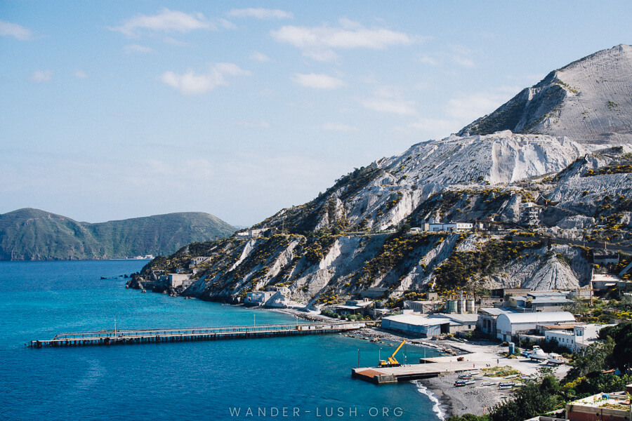 White cliffs and a jetty sticking out in the sea.