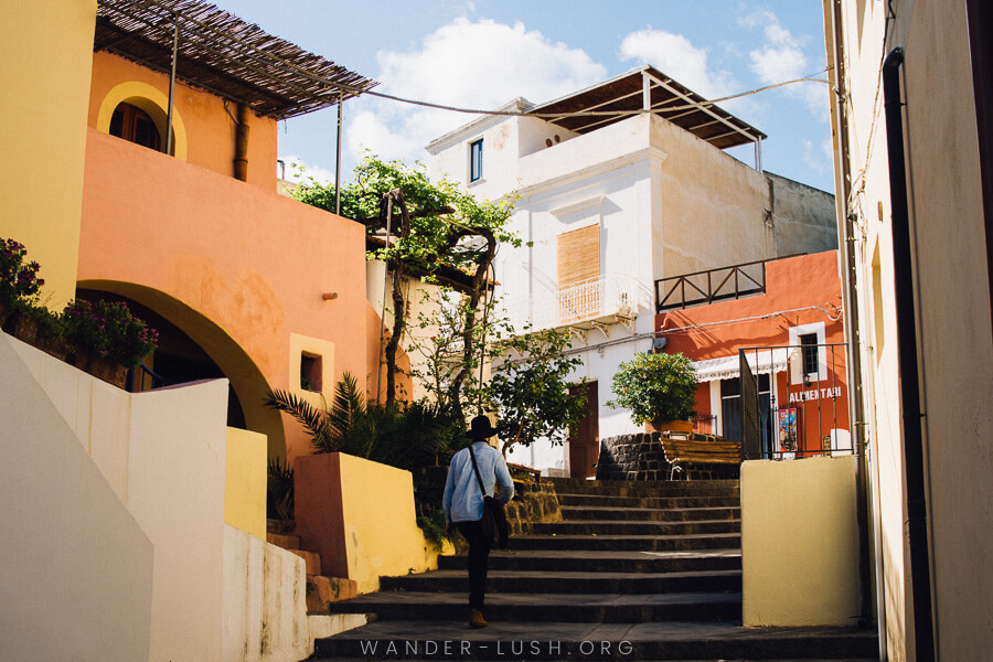 A man walks up a set of stairs amoungst yellow, white and orange buildings.