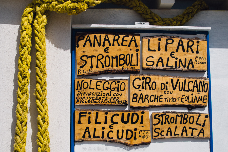 A wooden sign advertising tours in the Aeolian Islands.