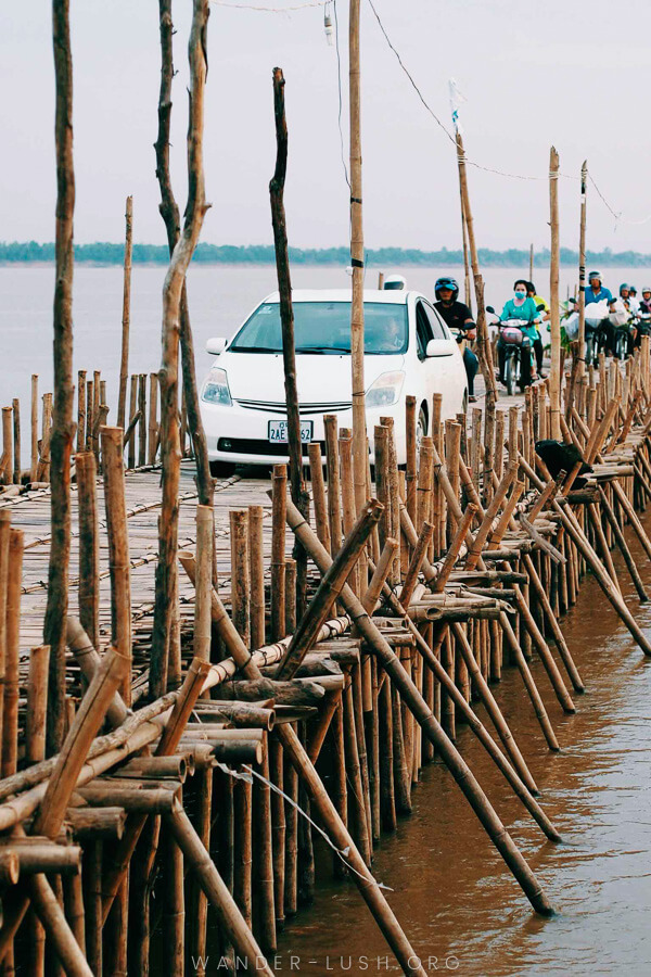 A white car leads as a group of motorcyclists ride over the Kampong Cham bamboo bridge.