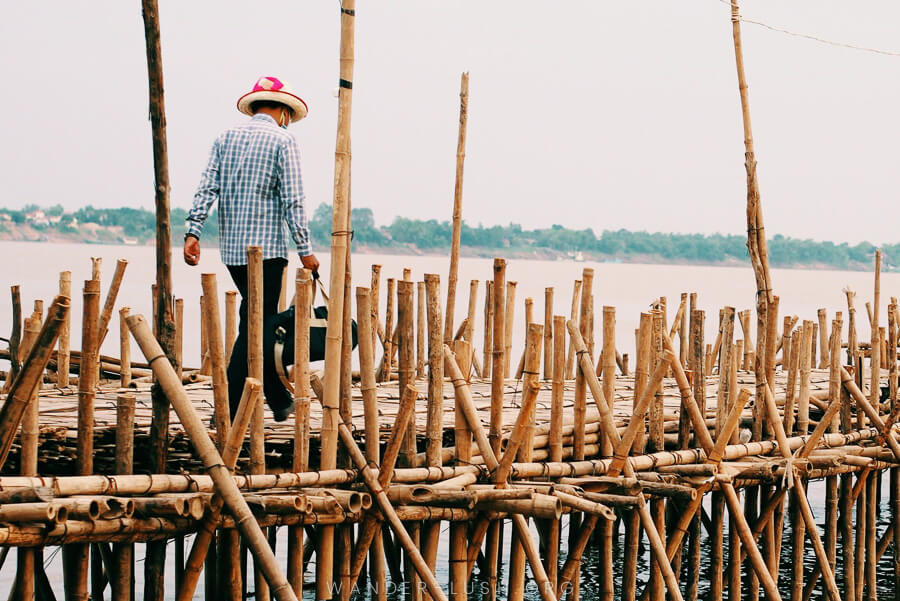 A single man in a straw hat walks across the Kampong Cham bamboo bridge, a huge bridge made of bamboo.