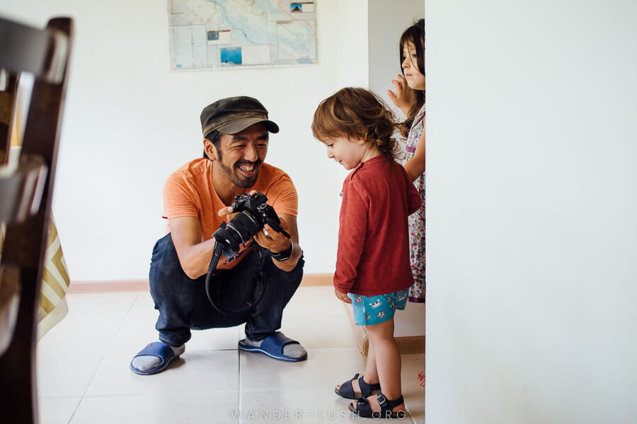A man shows two children their photo on his digital camera.