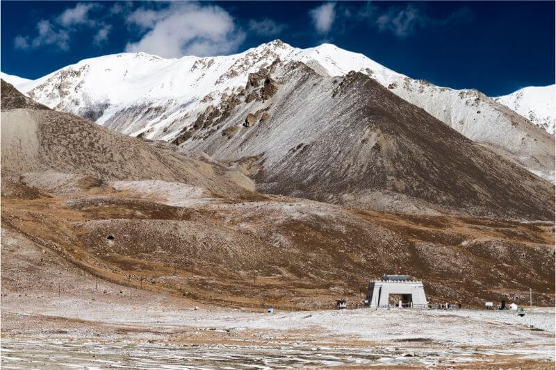Snow-capped mountains and a small man-made structure at the Pakistan-China border crossing.